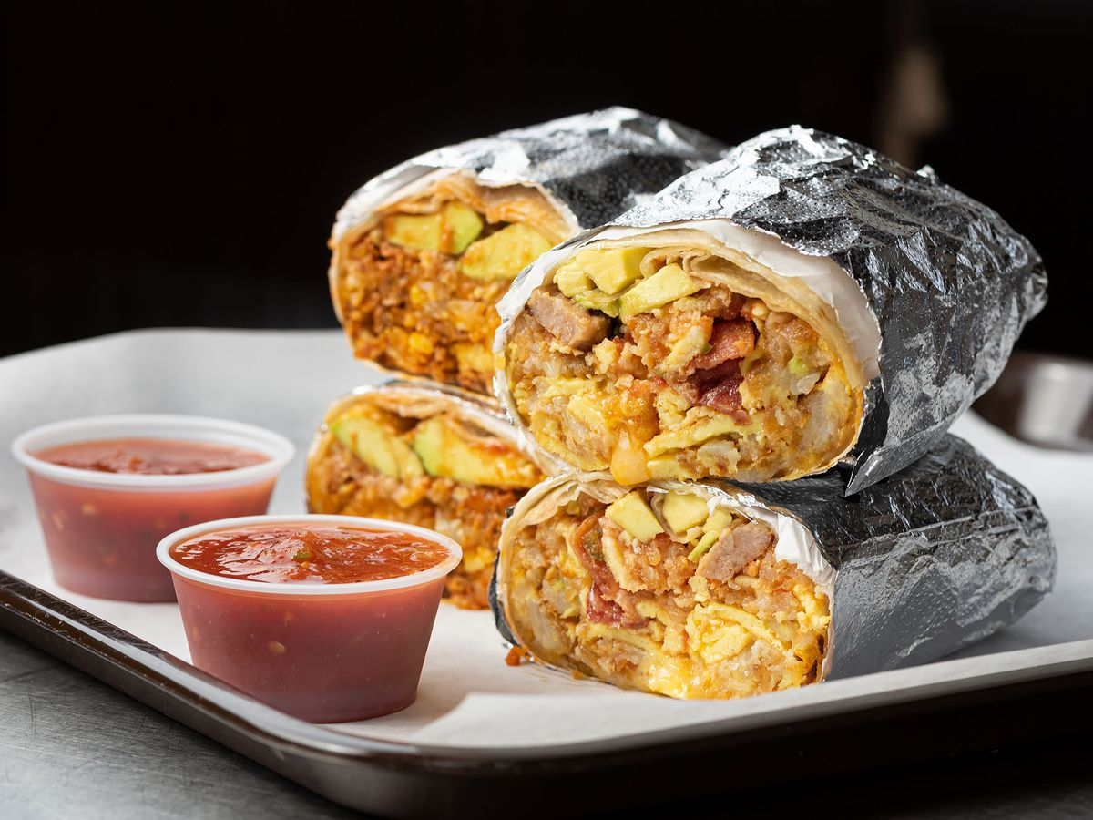 Breakfast burritos filled with bacon and sausage stacked atop one another.