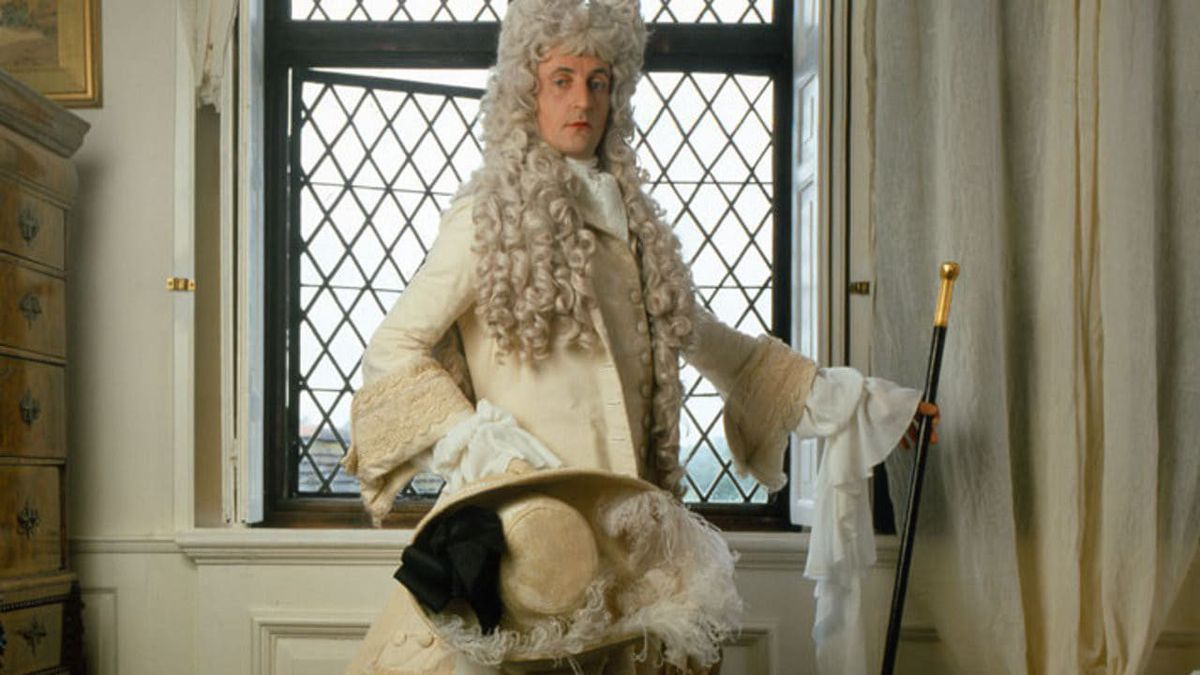 The Draughtsman's Contract: A man in a wig holds up his cane as he poses