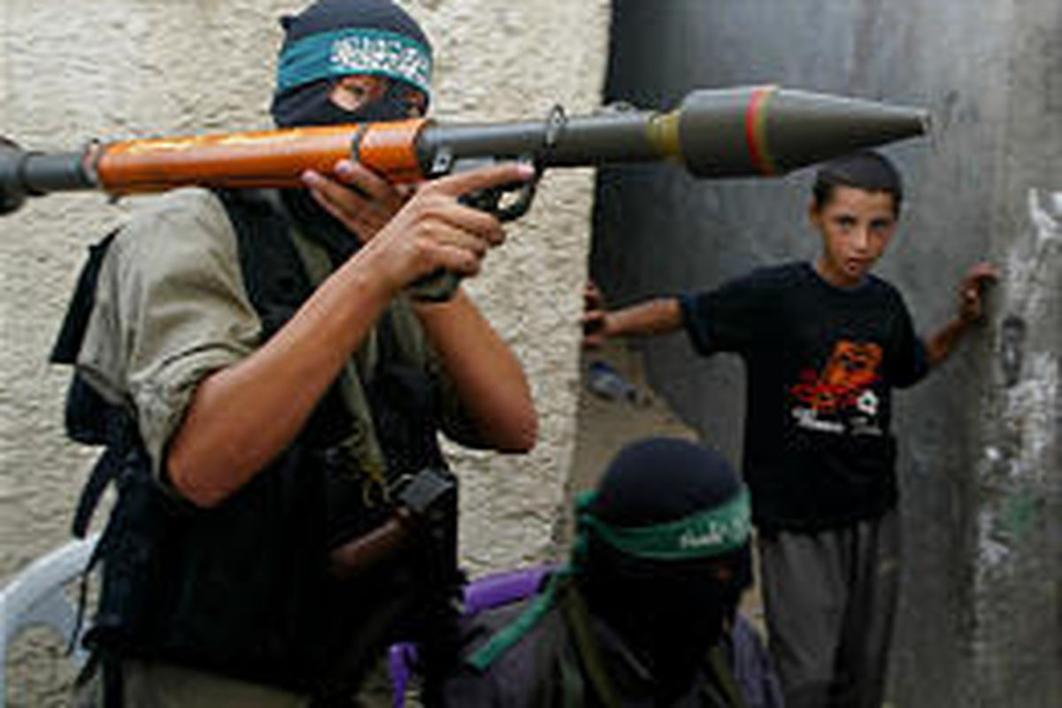 A militant from the Hamas group carries an anti-tank weapon through alleyways in Jebaliya refugee camp, northern Gaza.
