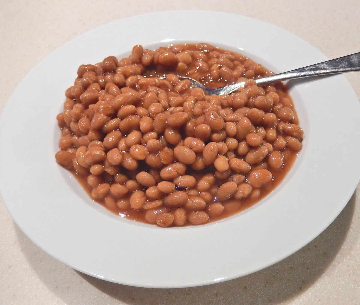 a bowlful of boston baked beans with a spoon