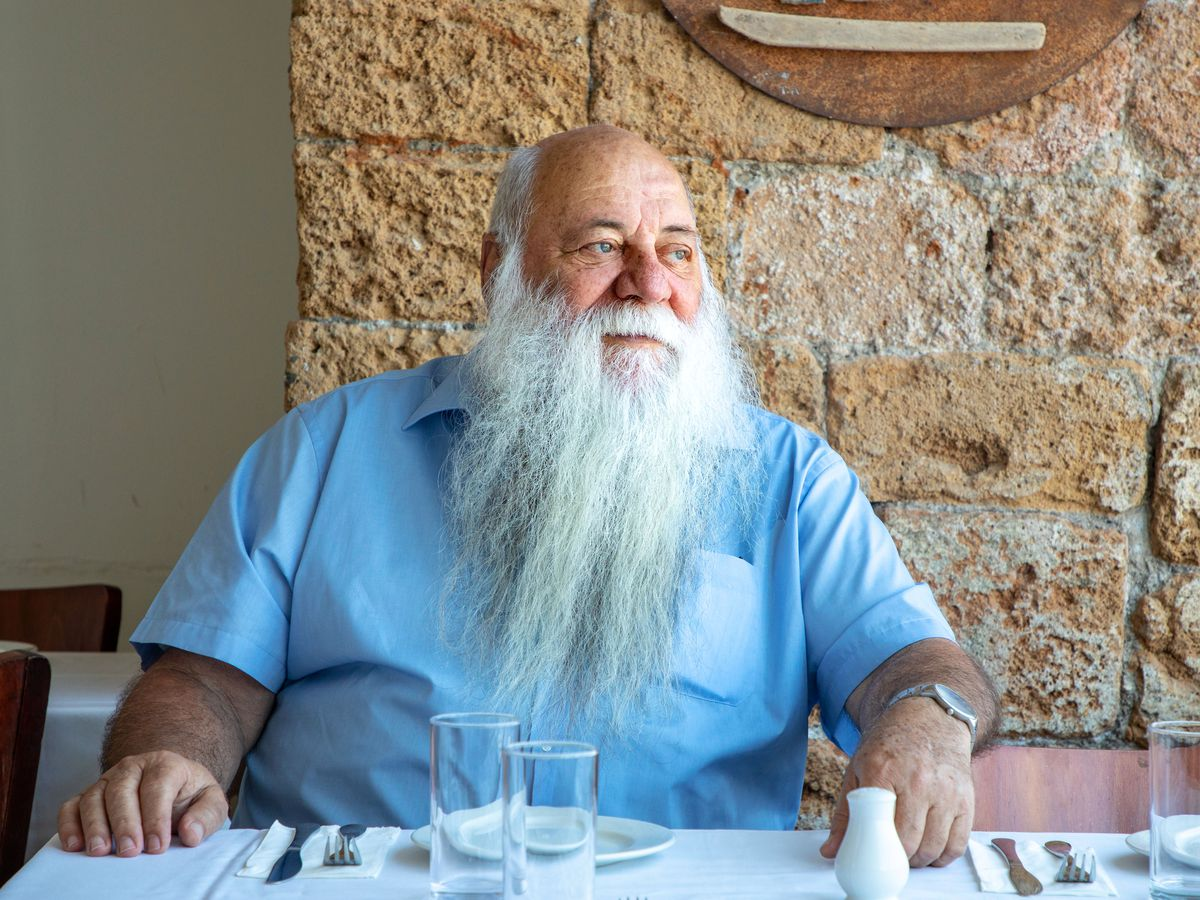 A man with a long white beard in a short-sleeved button down sits at a set table in front of an exposed brick wall