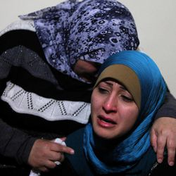 The sister, right, and an unidentified relative mourn for Ali Shaaban, a  television cameraman working for Al-Jadeed TV who was shot dead on the Lebanon-Syria border, at their home in Beirut, Lebanon, Monday, April 9, 2012. Shaaban was killed when the channel's film crew came under fire in the border area of Wadi Khaled, the channel's head of news said.