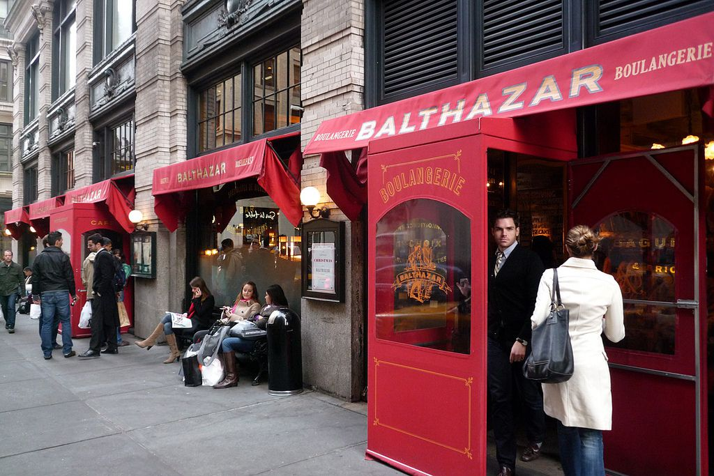 The entrance to Balthazar with a red awning