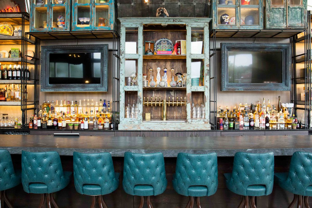 Photo of a restaurant interior, featuring a bar with teal leather high-top seating and weathered wood features
