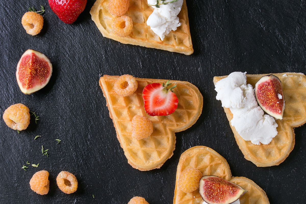 Wafers as heart shape with yellow raspberries, strawberries, sliced figs and ricotta cheese over black stone slate background. Top view. Square image