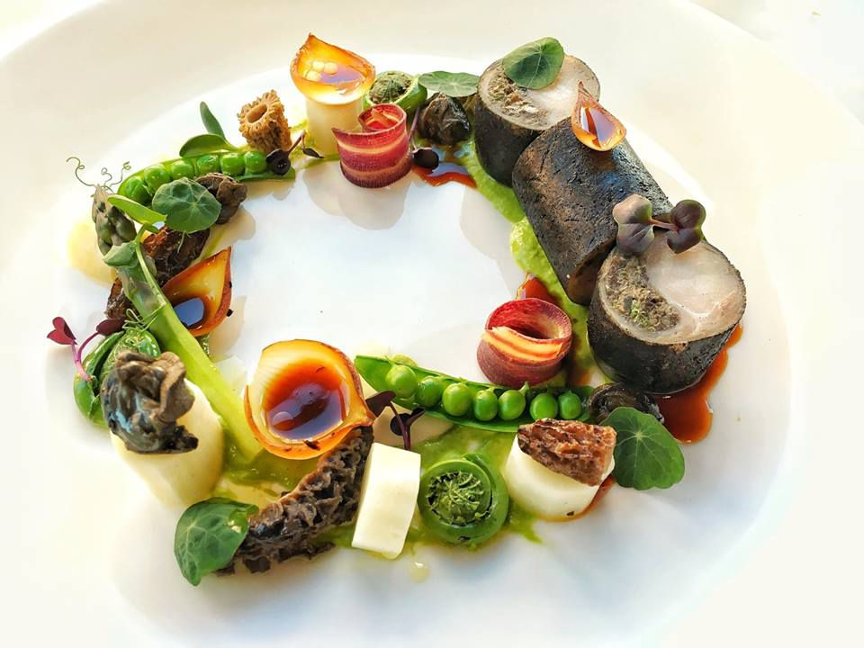 A circle formed from peas, scallops, and a rainbow of other ingredients