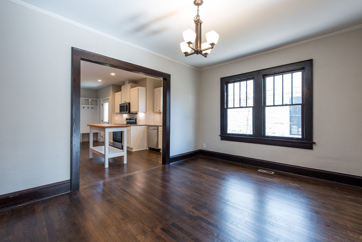 A large empty room with window chandelier, large window and entryway to the kitchen.