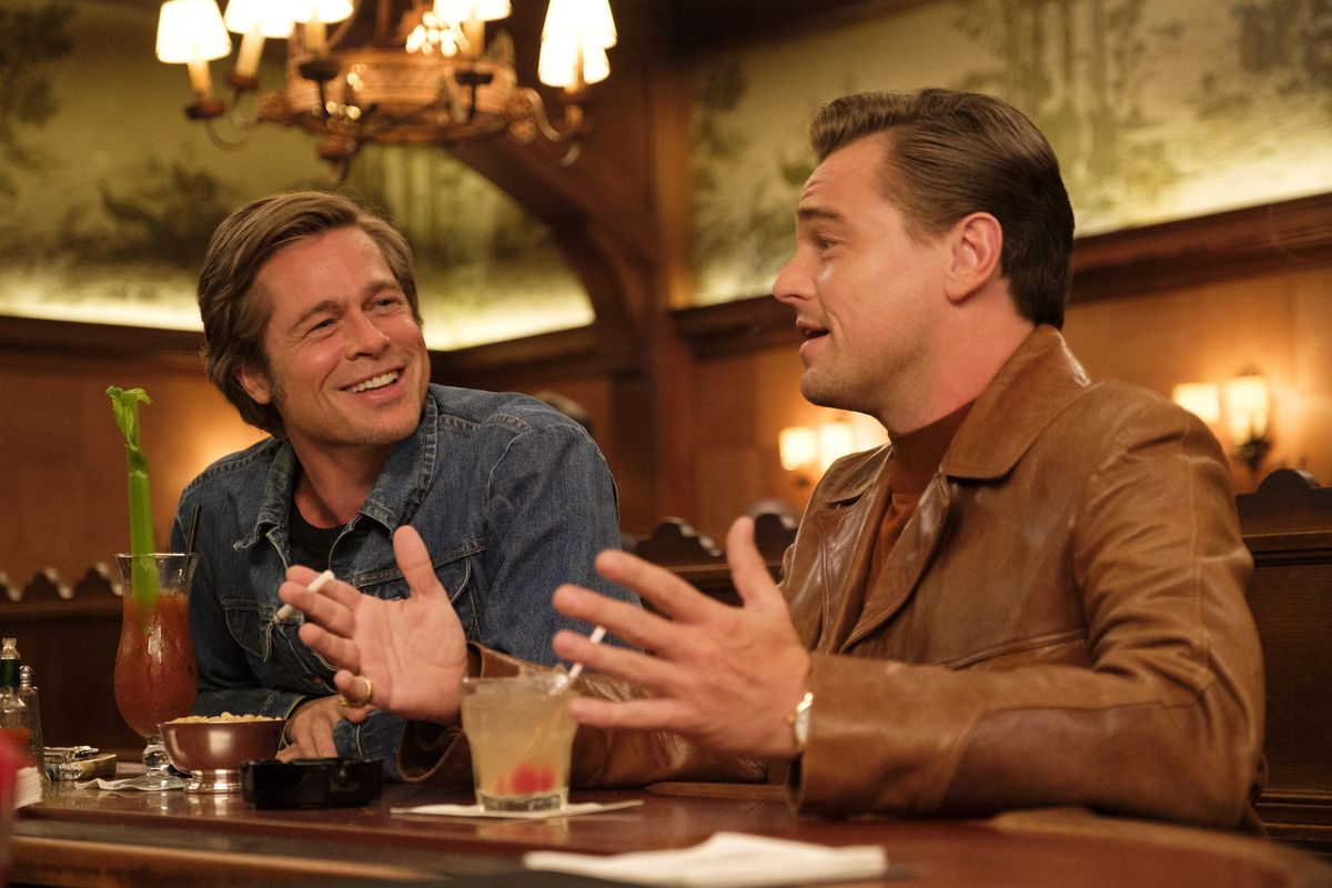 Cliff Booth (Brad Pitt) listens to Rick Dalton (Leonardo DiCaprio) tell a story as the two sit at a bar in Once Upon a Time in Hollywood