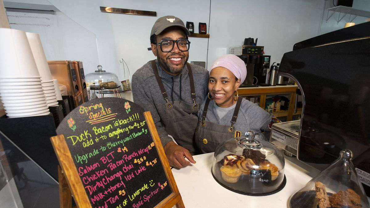 Two smiling folks behind a coffee counter.