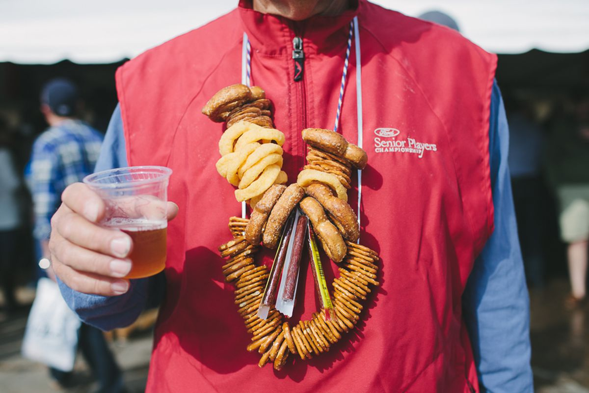 A person wears a pretzel necklace and a plastic cup of light beer at Michigan Brewers Guild festival in 2014.