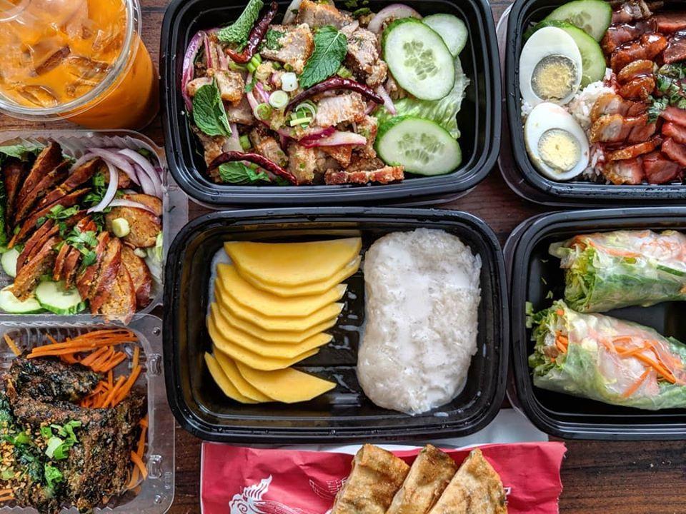 Overhead shot of a spread of takeout Thai food, including Thai iced tea, mango sticky rice, sai ua, and lots more