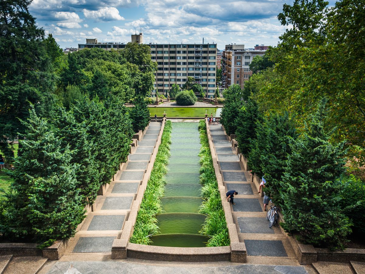 An aerial view of Meridian Hill Park in Washington D.C. There is a fountain surrounded by a path and trees. In the distance is a large building.