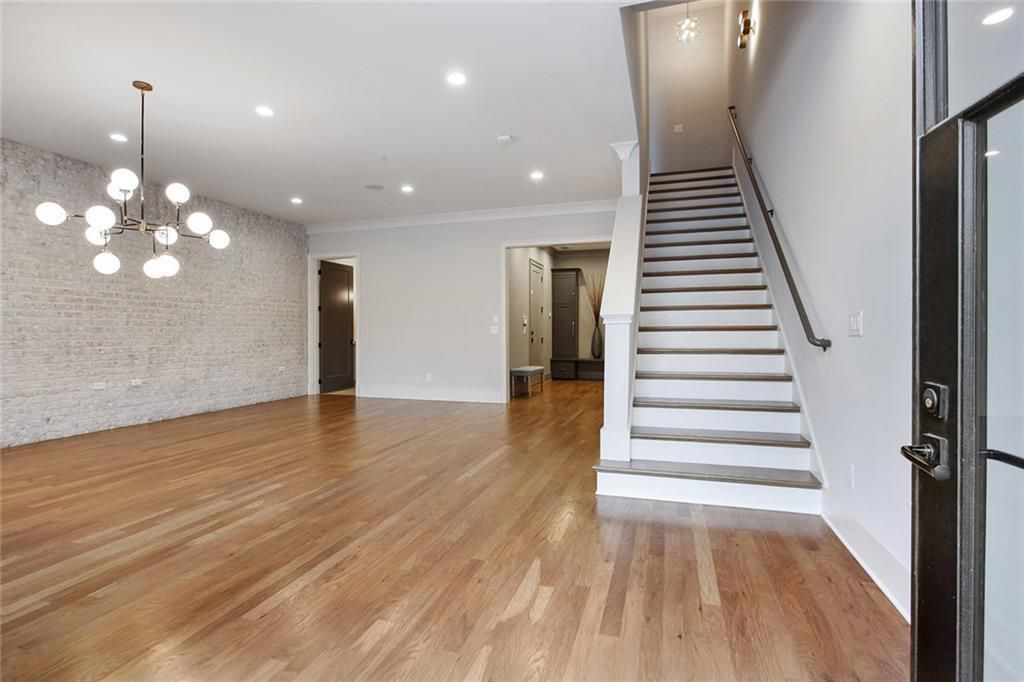 A big white room with wood floors and a chandelier.