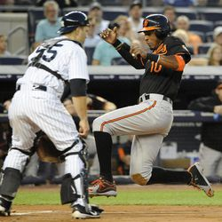 Baltimore Orioles' Adam Jones (10) scores at home plate ahead of the throw to New York Yankees catcher Russell Martin on a single by Chris Davis in the second inning of a baseball game on Friday, Aug., 31, 2012, at Yankee Stadium in New York.