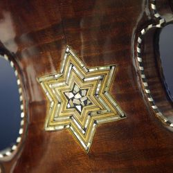 In a Monday, April 9, 2012 photo, the back of a violin showing a Star of David is shown on display at the Violins of Hope exhibit at UNC Charlotte in Charlotte, N.C. Eighteen violins recovered from the Holocaust and restored by  Israeli violin maker Amnon Weinsten make their U.S. debut on Sunday, April 15. Some were played by Jewish prisoners in Nazi concentration camps, while others belonged to the Jewish Klezmer musical culture. (AP Photo/Chuck Burton)