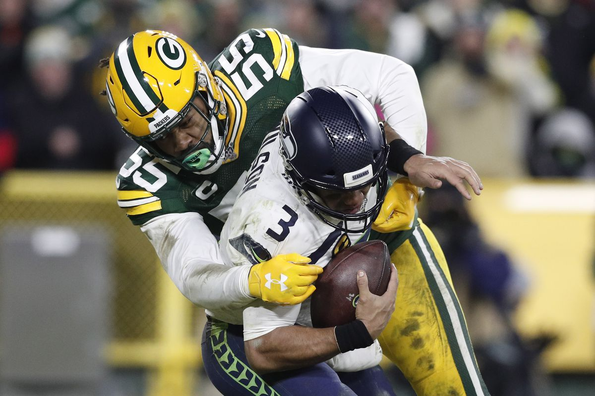 Seattle Seahawks quarterback Russell Wilson is tackled by Green Bay Packers outside linebacker Za'Darius Smith in the third quarter of a NFC Divisional Round playoff football game at Lambeau Field.