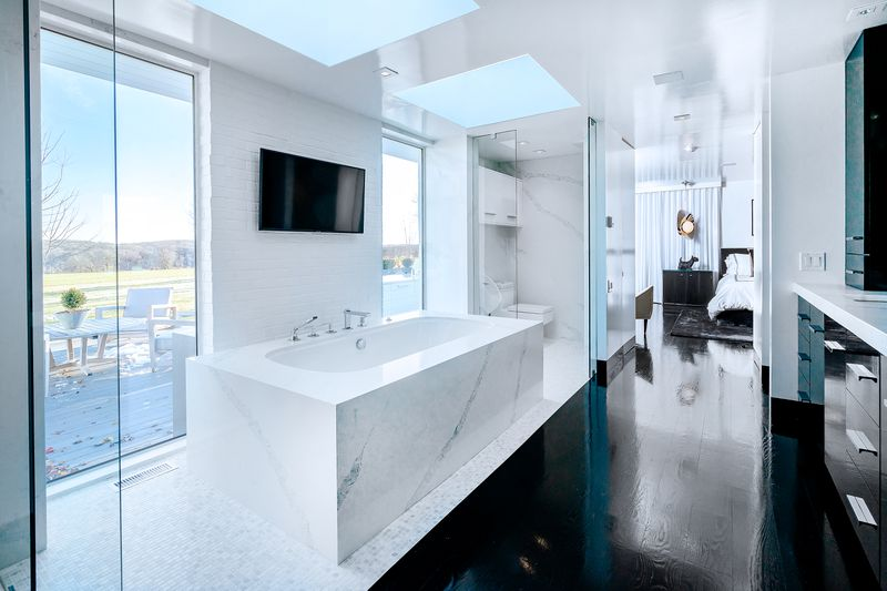 A large white marble soaking tub has windows on either side and a TV mounted above it.