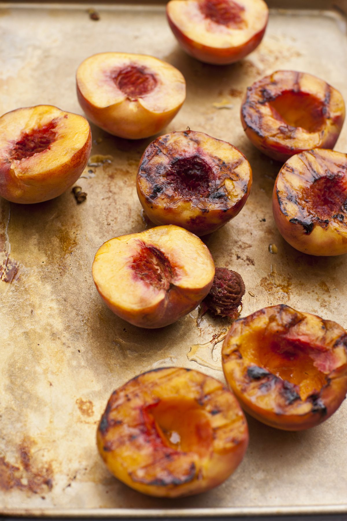 Several grilled peaches sit cut-side up on a baking tray, with grill marks visible on some of the peaches.