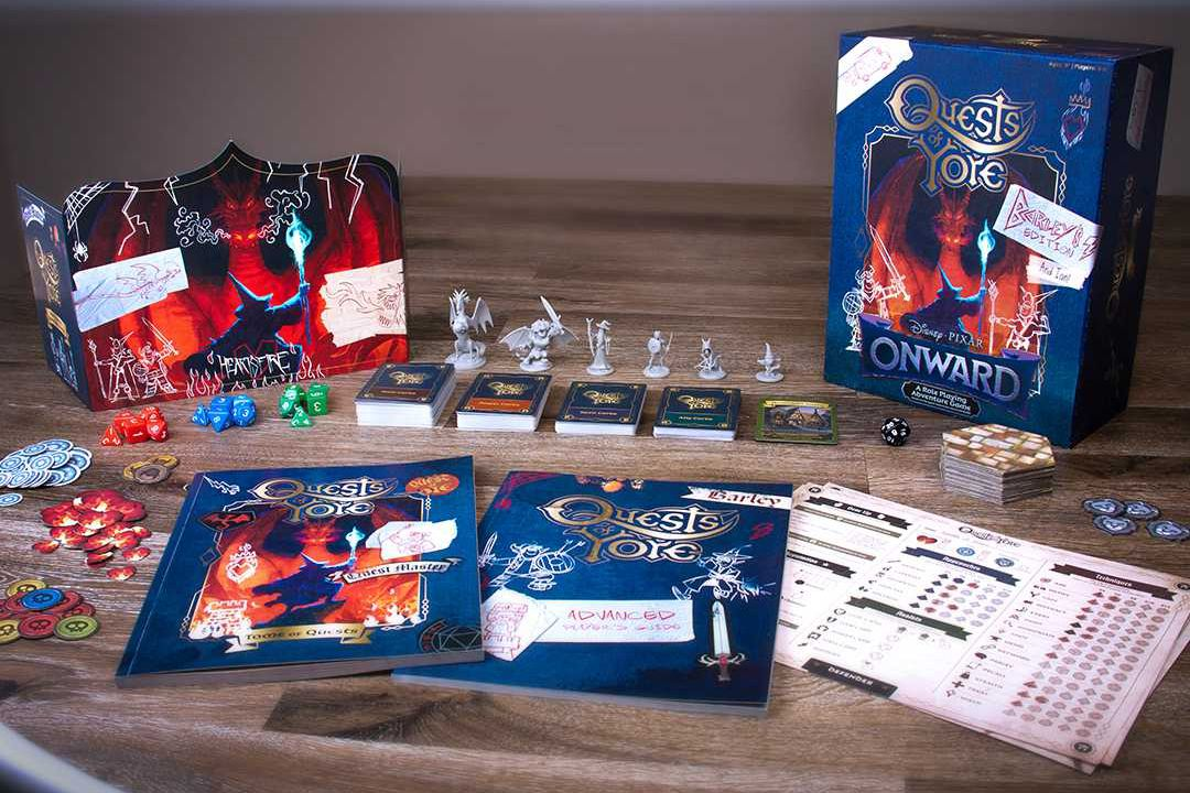 The contents of Quests of Yore spread out for play. They include cards and dice, as well as plastic miniatures of the characters from the movie.
