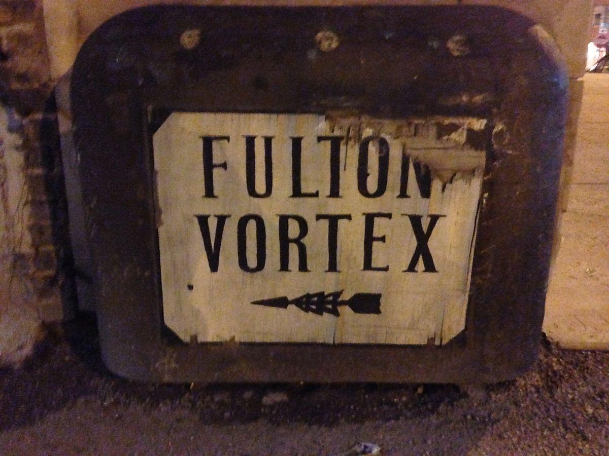 A photo of a worn sign that reads: Fulton Vortex. There is an arrow pointing towards the site.