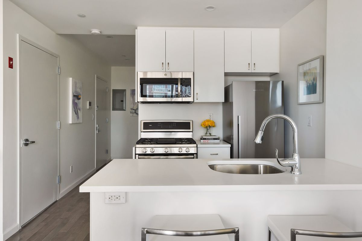A kitchen with white cabinetry and an island.