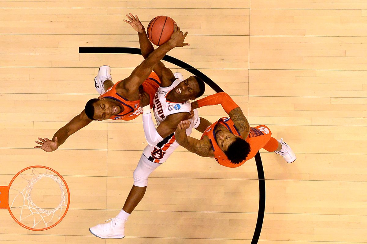 Three basketball players go up for the ball.