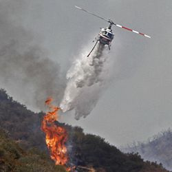A firefighting helicopter drops a load of water on a flair-up along Camp Bonita Road in Angeles National Forest, Calif. near Azusa on Tuesday, Sept. 4, 2012.  It could be a week before firefighters can contain the 3,800-acre blaze because of high temperatures and rugged terrain in thick brush that hasn't burned in a couple of decades.