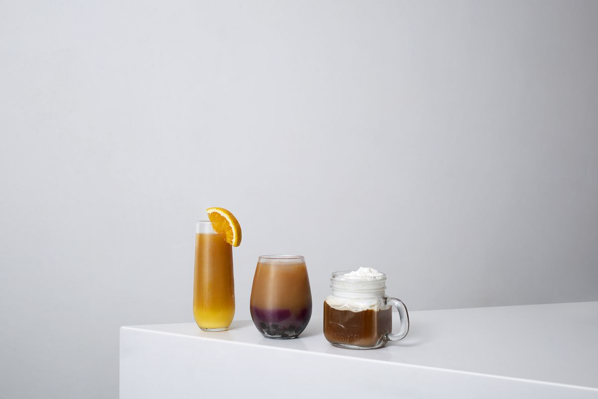 Three colorful drinks sit on the edge of a white counter top