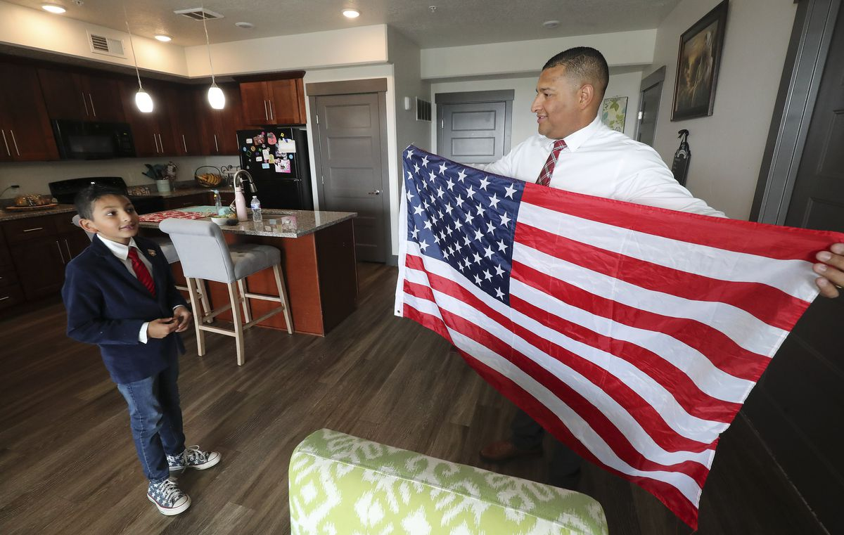 Carlos Moreno shows his son, Carlos Isaias, an American flag at their home in Midvale on Monday, Sept. 9, 2019.