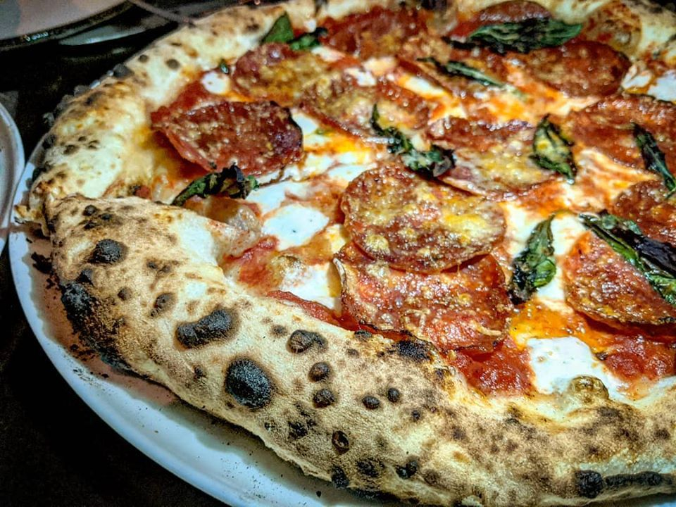 Closeup of Neapolitan-style pizza with a leopard-spotted, puffy crust. Toppings include pepperoni and basil.