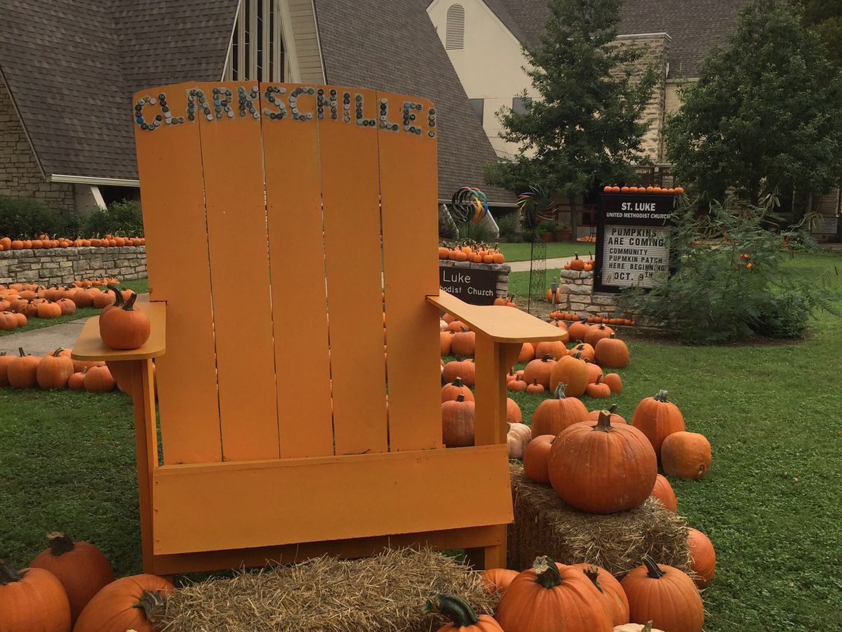Big adirondack chair surrounded by pumpkins with church in back