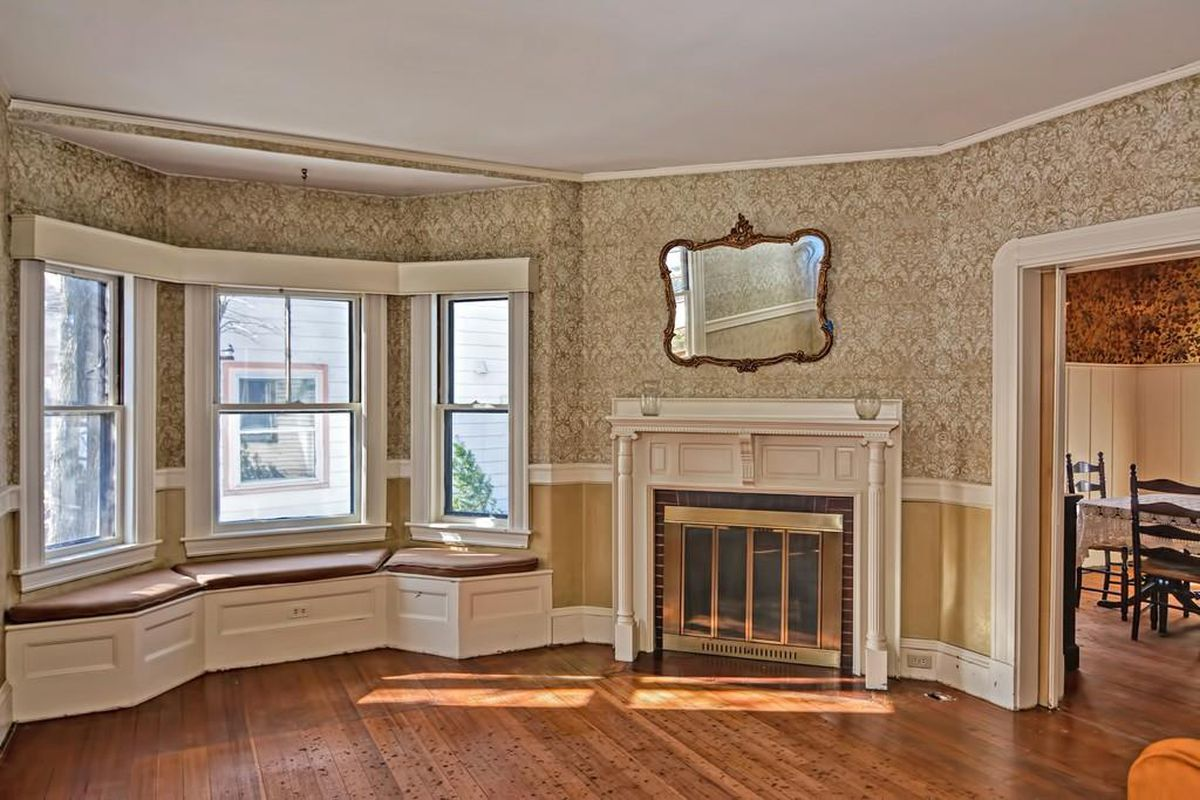 An empty parlor with a fireplace, a mirror above the fireplace, and a bay window.