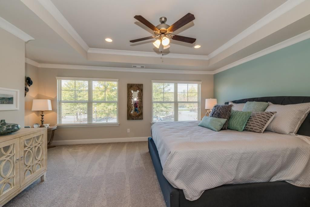A large light blue master bedroom with tray ceilings.