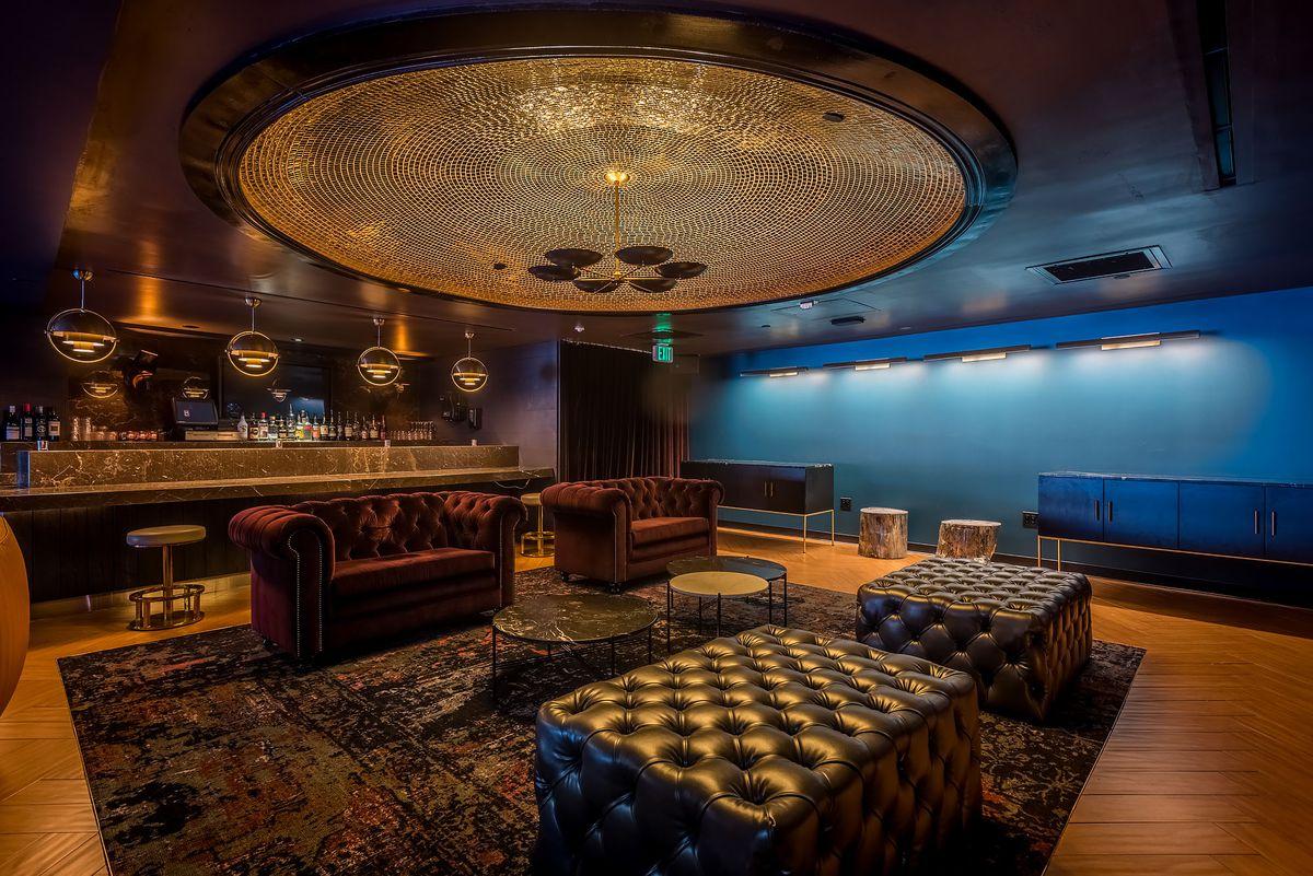 A golden glow a bar inside of a venue.
