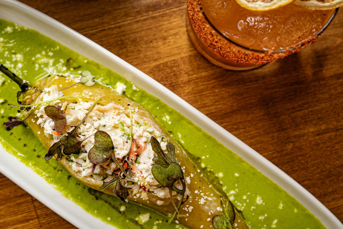 A chile relleno stuffed with crab salad and covered in green salsa
