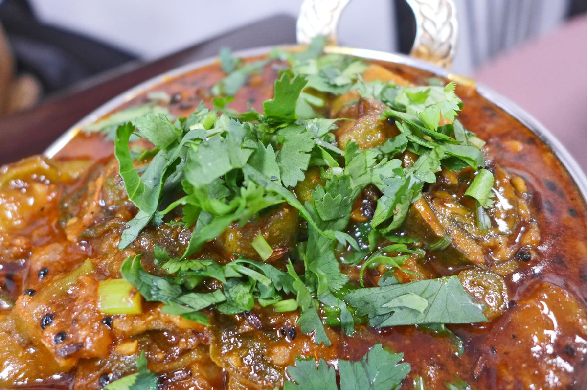 A bowl of brownish, stew-like food with a sprinkling of cilantro leaves on top