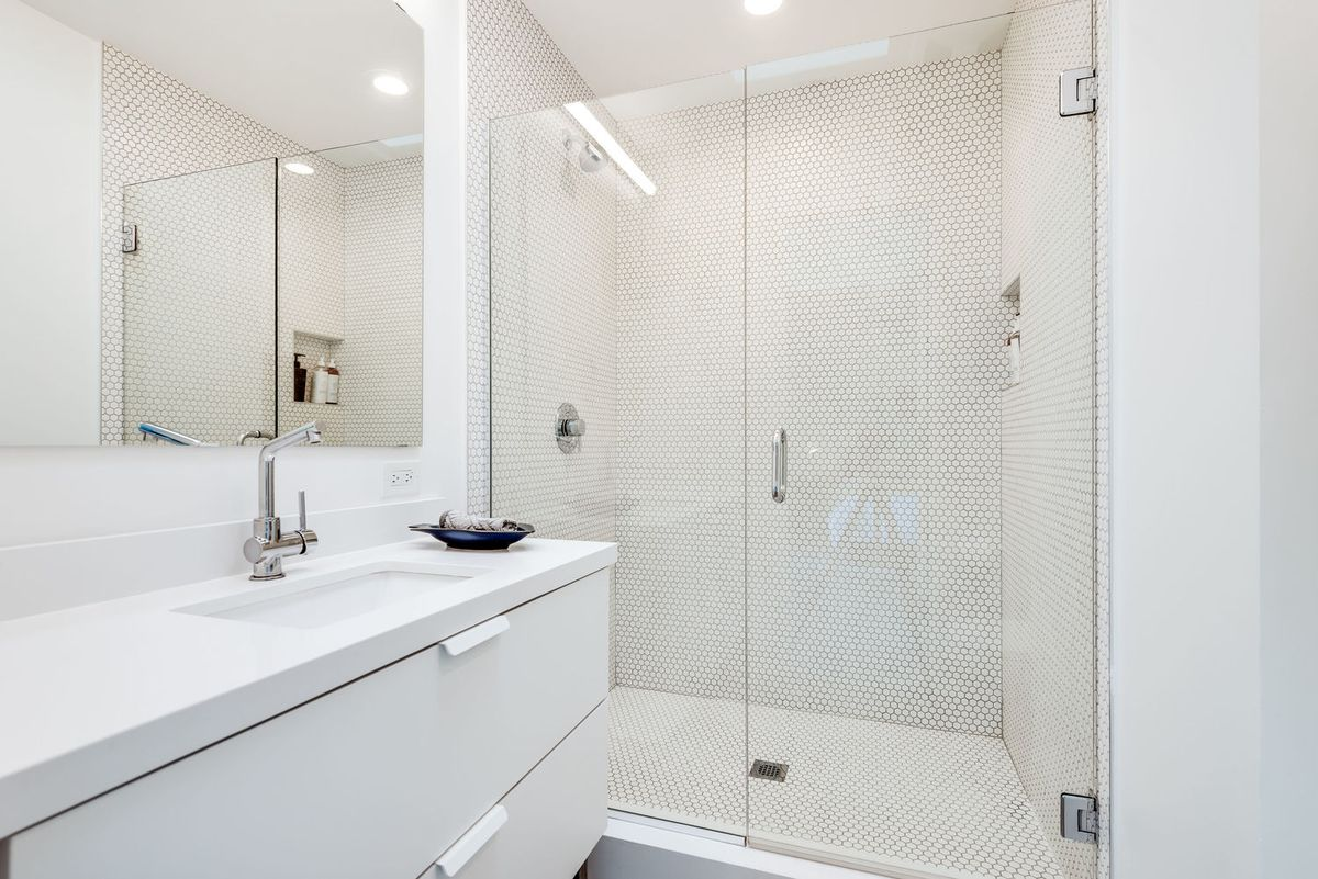 An all-white bathrooms has one sink and a glass walk-in shower.