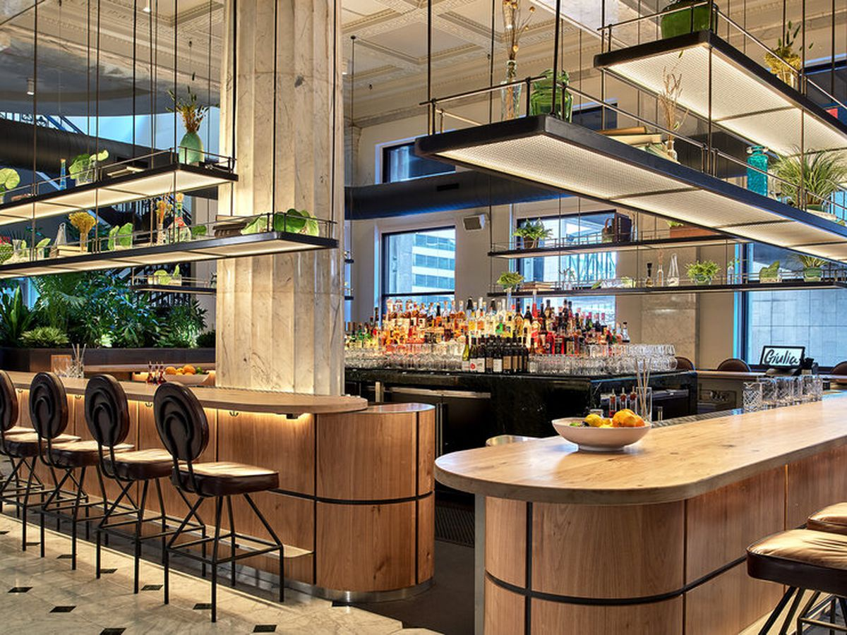 The glossy bar at Giulia is framed with thick white columns, alcohol, and plants.