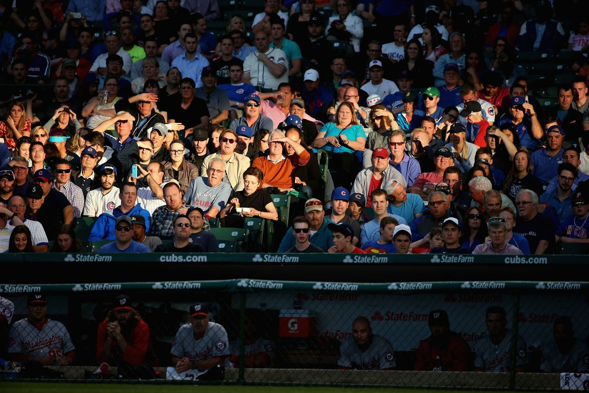 Fans sit in the setting sun as the Chicago Cubs take on the Washington Nationals