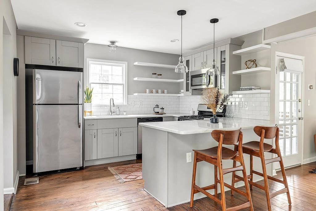 A white and gray kitchen with wood chairs.
