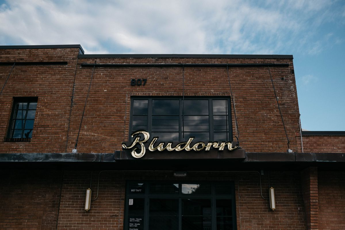 """A large, square brick building with tall windows and an overhang with a vintage-looking sign reading """"Bludorn"""""""
