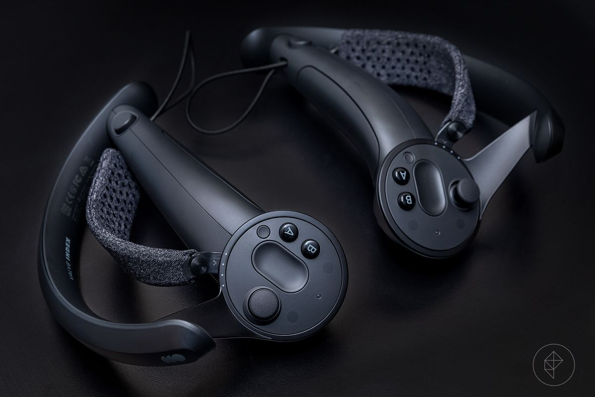 a photo of two Valve Index controllers, which include a cloth strap inside the hand grip, on a black background