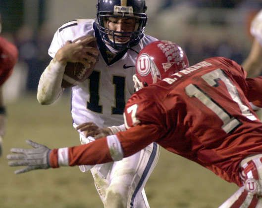 BYU's Brandon Doman goes head to head with Utah's Arnold Parker during the Utah v. BYU game at Rice-Eccles Stadium at the University of Utah, Friday, November 24, 2000.
