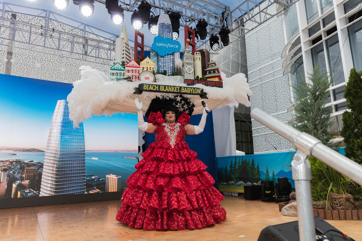 A performer in a giant novelty hat of the San Francisco skyline, with a model of Salesforce Tower at center.