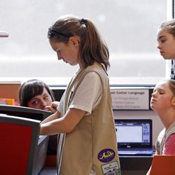 Girl Scouts work at a laser wood cutting machine. | AP Photo