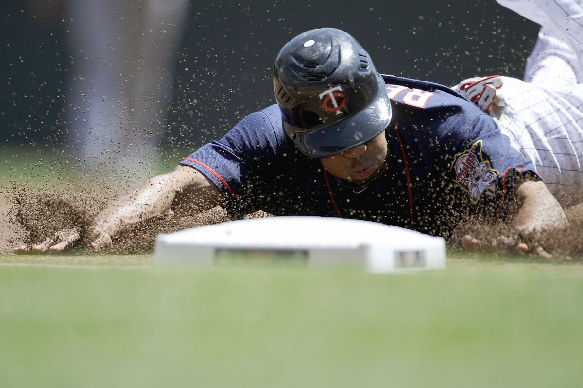 MINNEAPOLIS, MN - JULY 29: Ben Revere #11 of the Minnesota Twins steals third base during the first inning of the game against the Cleveland Indians on July 29, 2012 at Target Field in Minneapolis, Minnesota. (Photo by Hannah Foslien/Getty Images)