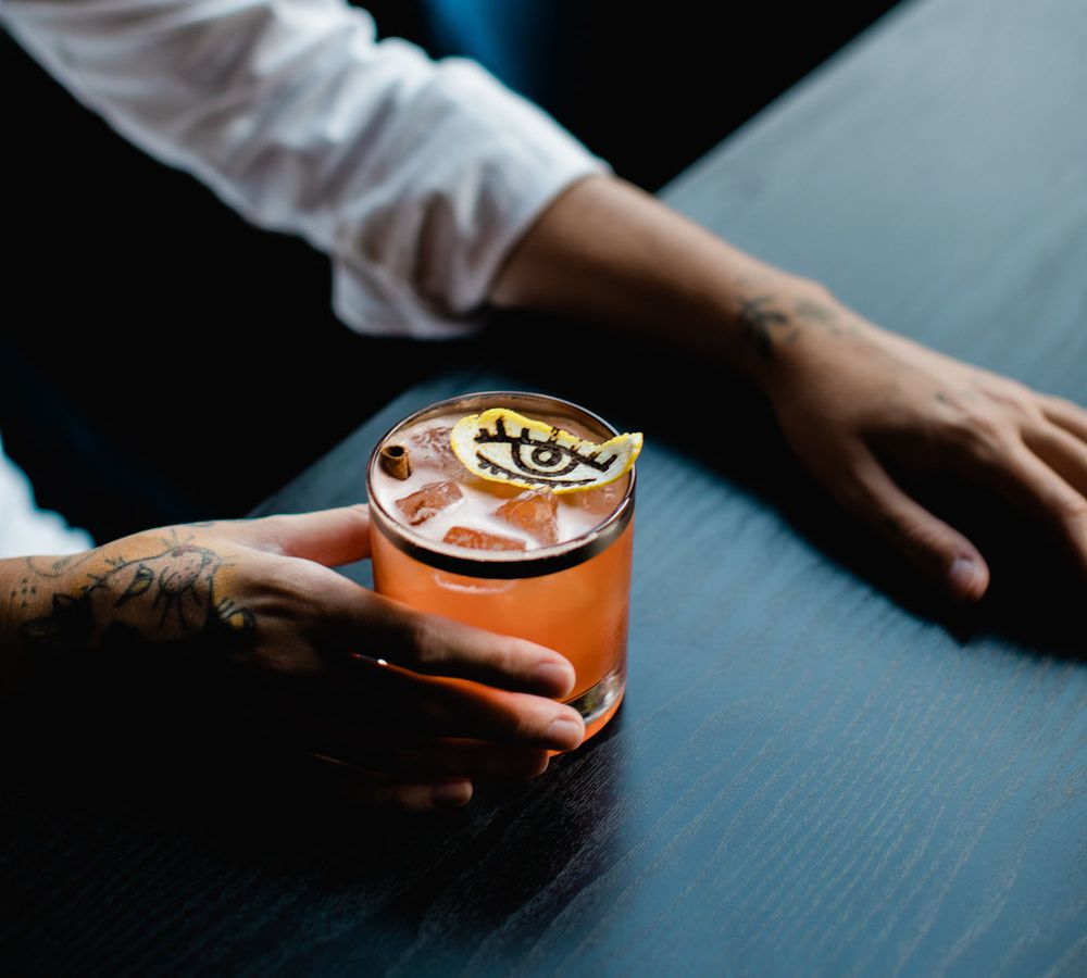 A tattooed hand holds a cocktail garnished with a citrus slice stamped with an eye outline