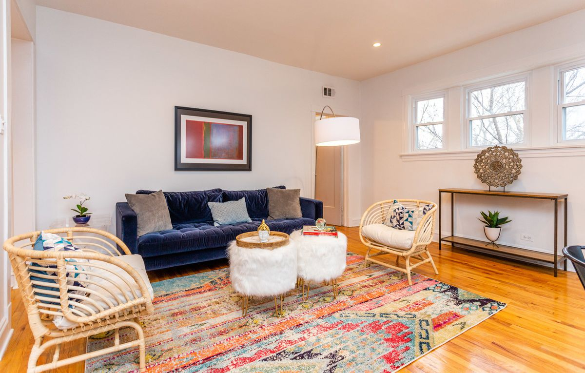 A blue velvet sofa stands between two wicker chairs on a colorful rug with two white furry poufs in the middle.