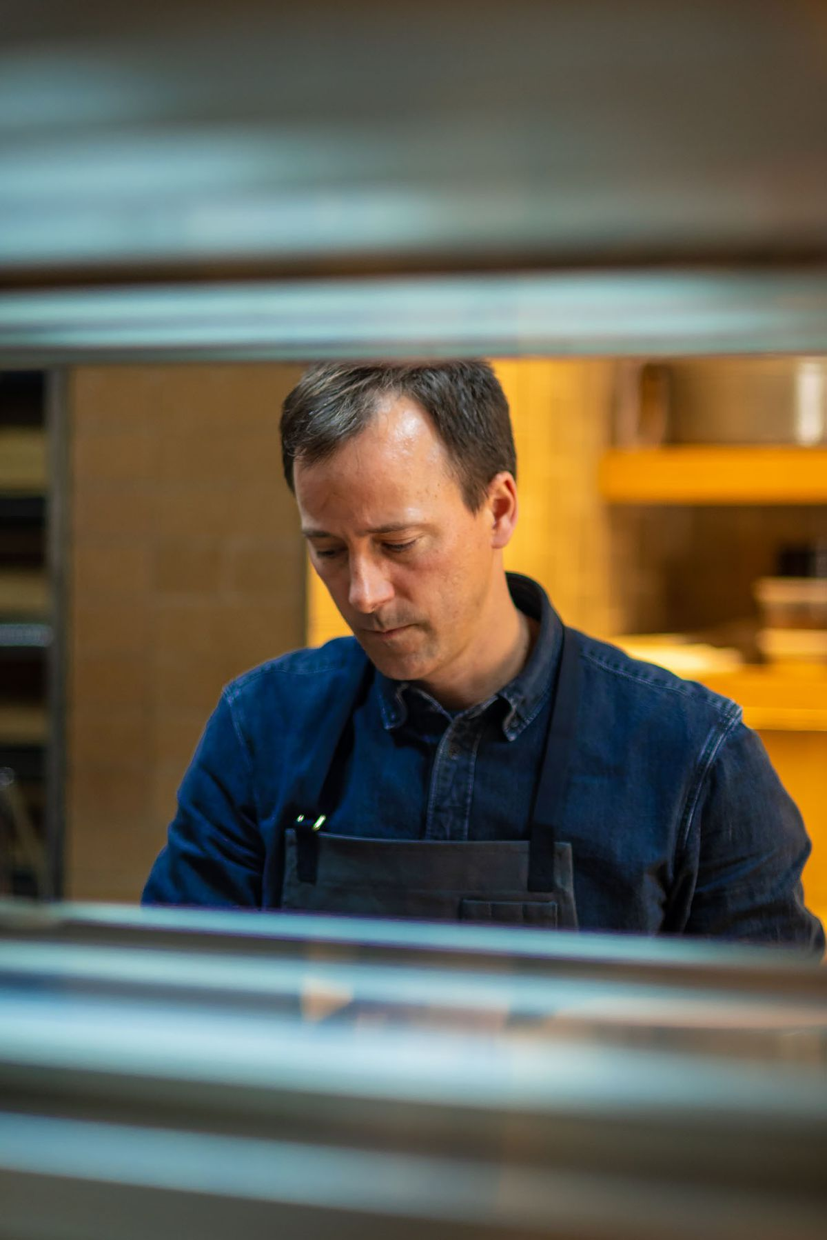 Eric Bost, chef, framed with stainless steel kitchen equipment at Auburn restaurant in LA.