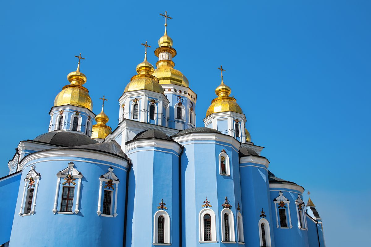 """The exterior of <span data-author=""""843"""">St. Michael's Golden-Domed Monastery in Ukraine. The facade is blue and the roof is gold with multiple towers and turrets. </span>"""